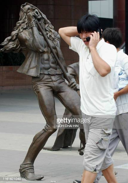 A man chats on his handphone as he walks pass one of the many sculptures along a street in Beijing 10 September 2002 Beijing is holding a display of...