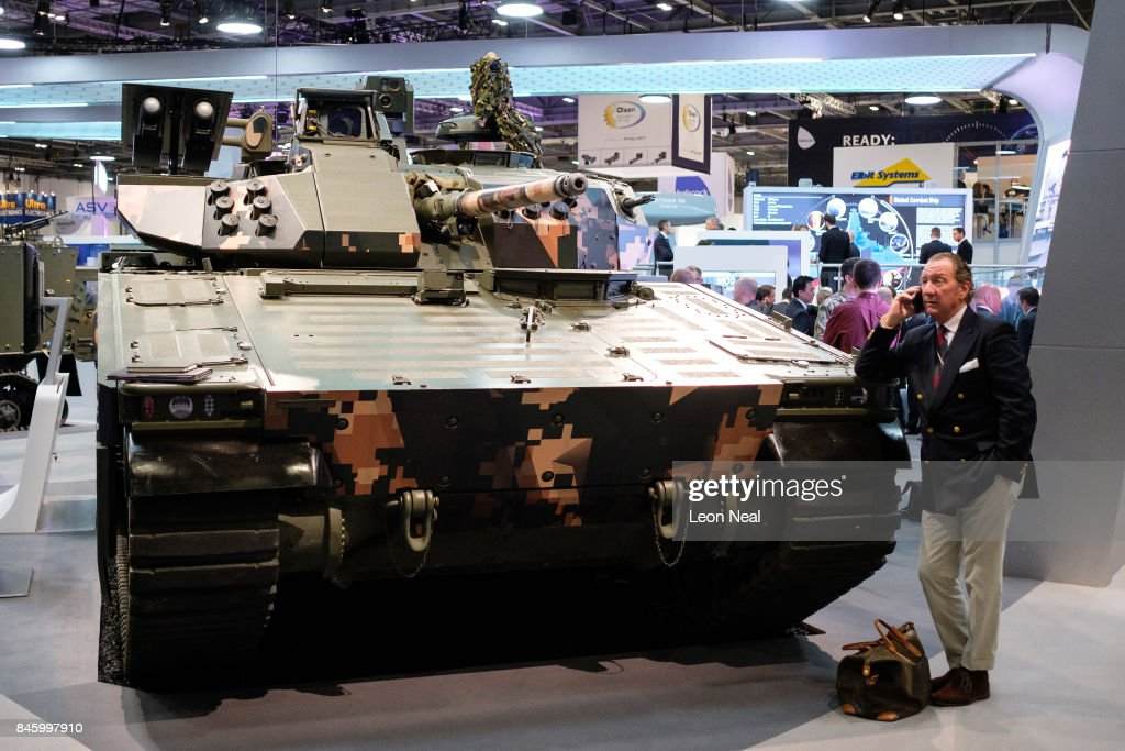A man chats on his phone as he leans on a CV90 Battle Station in the 'BAE Systems' display area at the DSEI event at the ExCel centre on September 12, 2017 in London, England. The annual weapons and security trade fair sees manufacturers of all aspects of military, naval, airforce and security from all over the world display their latest designs to delegates.