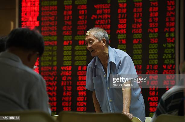 A man chats with fellow investors in front of a board showing stock market movements at a securities company in Beijing on July 10 2015 Chinese...