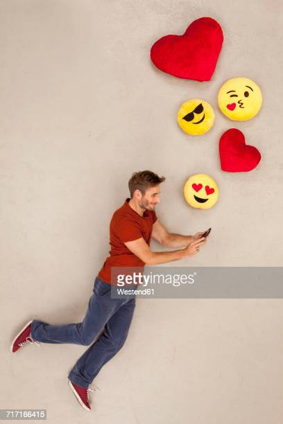 Man chatting on his smart phone, sending emojies