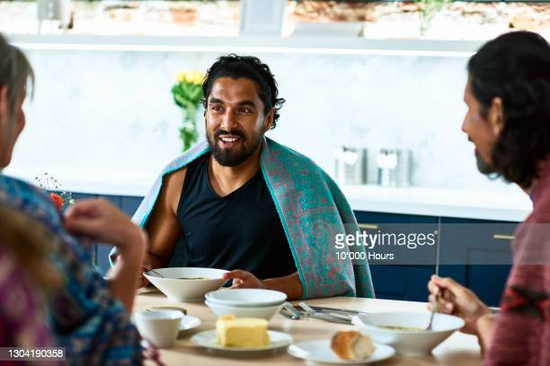 man chatting to friends over lunch after yoga session - mid adult men stock pictures, royalty-free photos & images