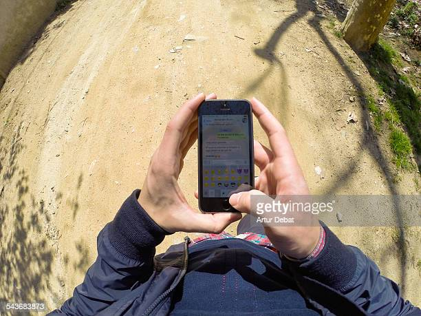Man chatting with WhatsApp application on smartphone using emoticons from personal point of view at the street