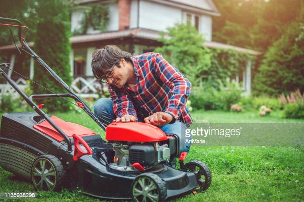 man checking a lawn mower in his back yard - lawn mower stock pictures, royalty-free photos & images