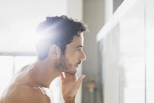 Man checking beard in bathroom mirror - gettyimageskorea