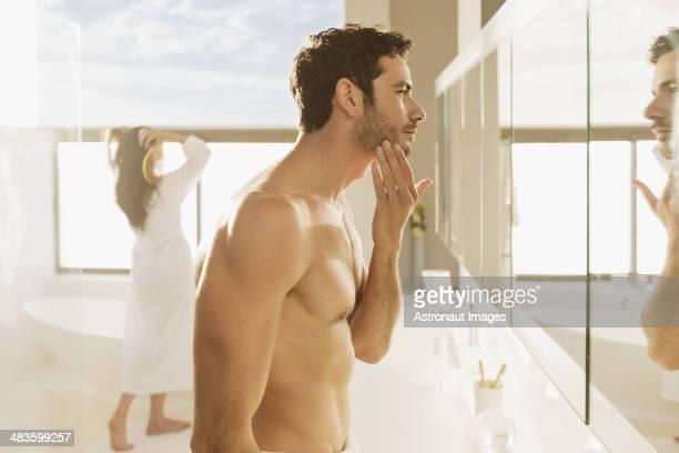 Man checking beard in bathroom mirror