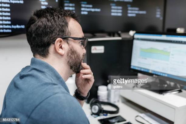 mann kontrollieren geschäftsdaten auf dem bildschirm im büro - börsenhändler stock-fotos und bilder
