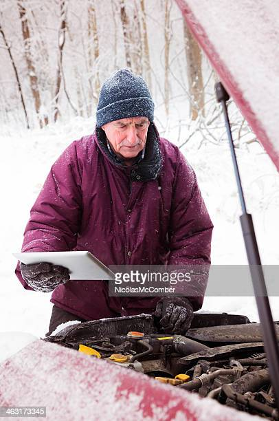 Man checking car engine with tablet