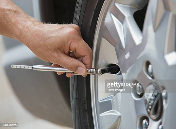 Man checking car tire pressure