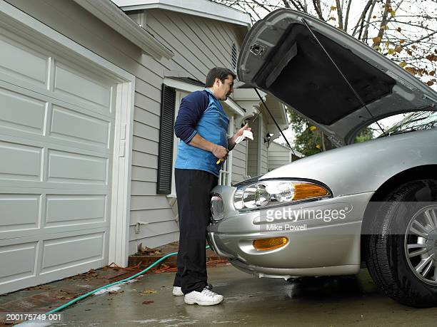 Man checking car's oil in driveway