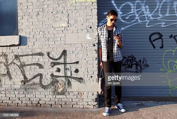 man checking cell phone near graffiti covered wal - williamsburg brooklyn fotografías e imágenes de stock