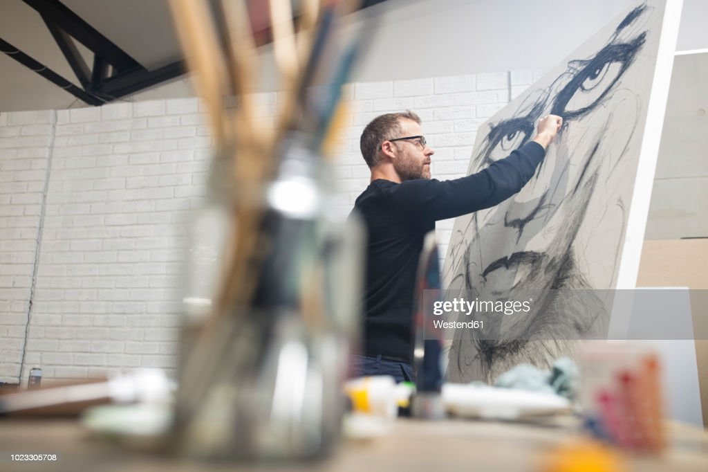 Man checking drawing in studio : Stock Photo