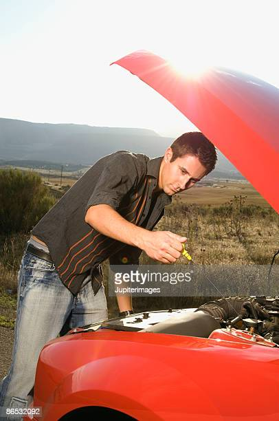 Man checking engine oil in car