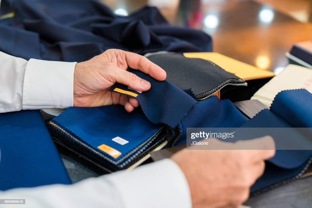 Man checking fabric swatches : Stock Photo