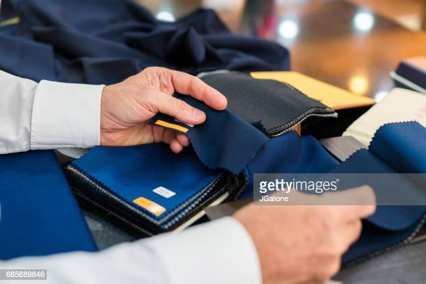 man checking fabric swatches - jgalione stock pictures, royalty-free photos & images