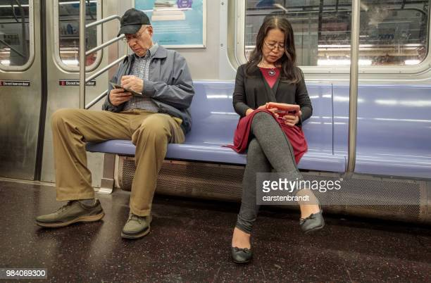 prüfen sein handy in der u-bahn saß eine lesung frau mann - bahnreisender stock-fotos und bilder