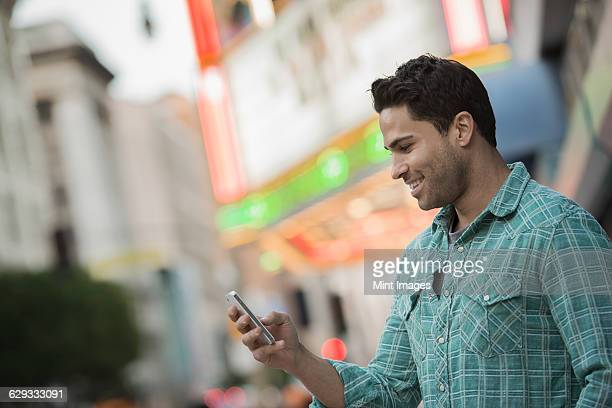 A man checking his phone on a city street.