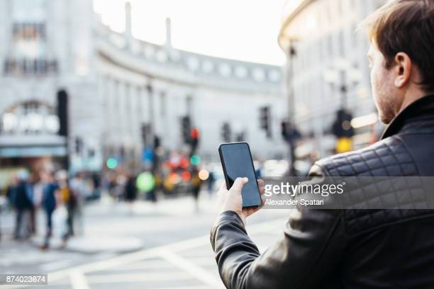 Man checking his phone on the street, rear view