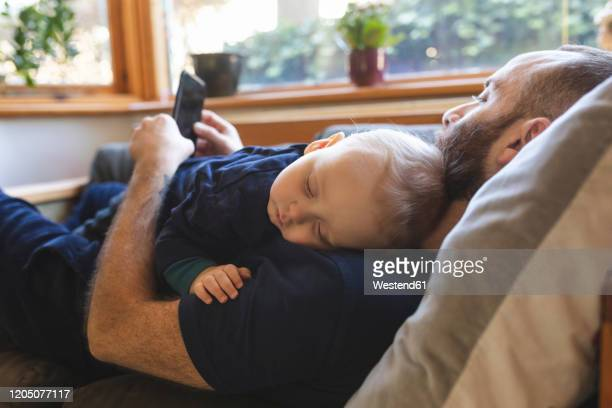 man checking his phone while his little baby son is sleeping on the sofa - candid forum stock pictures, royalty-free photos & images
