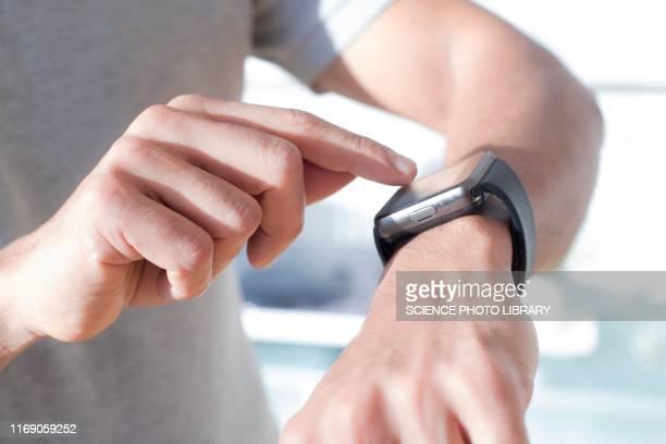 man checking his smart watch - スマートウォッチ ストックフォトと画像