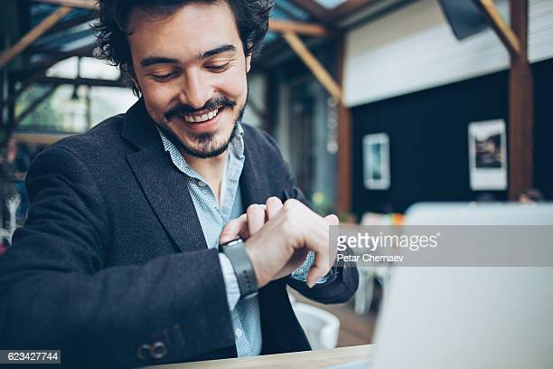 man checking his smart watch - temps qui passe photos et images de collection