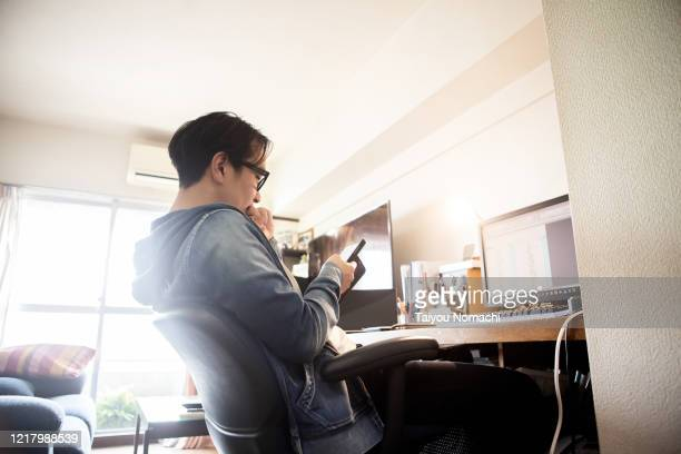 a man checking his smartphone while working from home - japanese ethnicity stock pictures, royalty-free photos & images