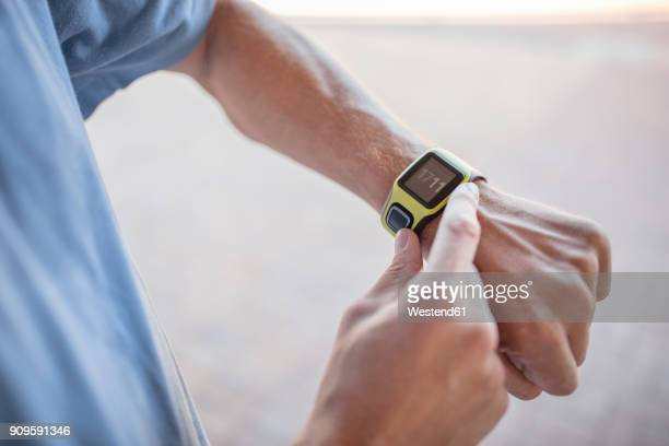 man checking his smartwatch before exercising - wrist watch stock pictures, royalty-free photos & images