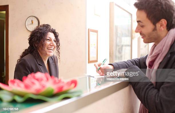 Man checking into hotel as receptionist smiles