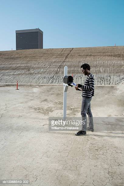 man checking mail in mailbox on construction site, smiling, side view - domestic mailbox stock pictures, royalty-free photos & images