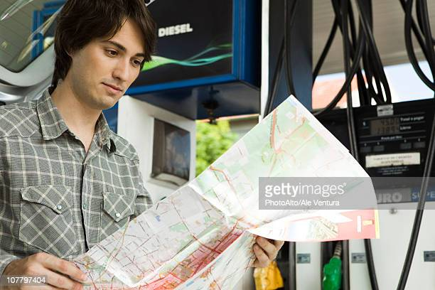 Man checking map at gas station