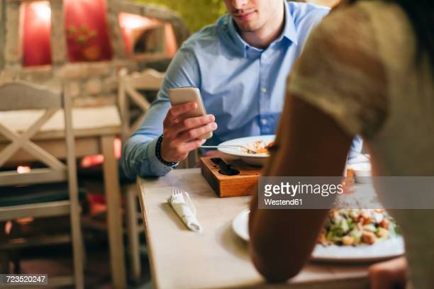 man checking messages while having dinner in a restaurant - dating stock pictures, royalty-free photos & images