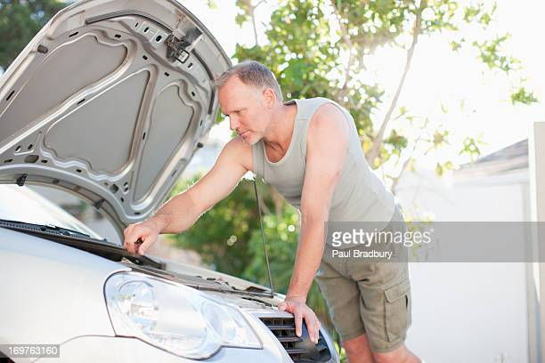 man checking oil in car - oil change stock pictures, royalty-free photos & images