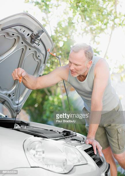 Man checking oil in car