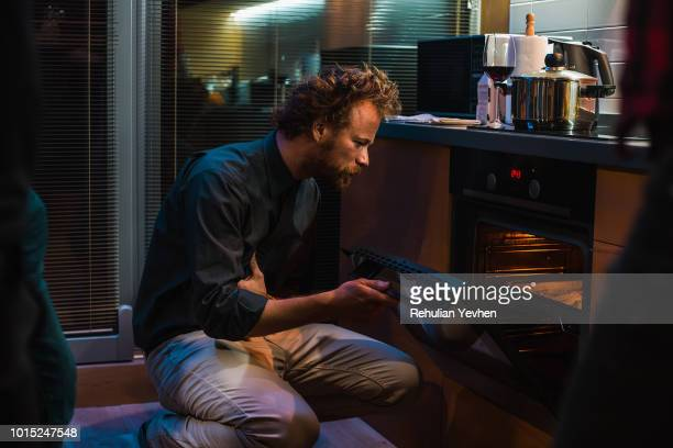 man checking on food in oven - oven stock pictures, royalty-free photos & images