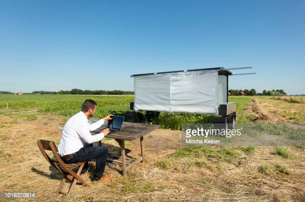 Man checking on robot monitoring crops and flowers on agricultural site in pixelfarming research