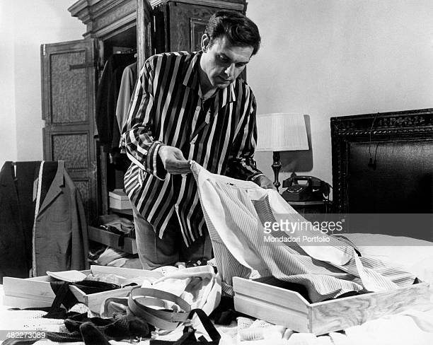 Man checking out carefully a skirt collar after he emptied two drawers of skirts and belts. Italy, 1960s