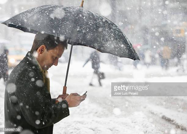 Man checking phone while in the snow