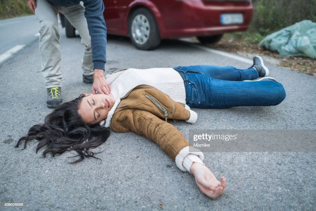 Man checking pulse of injured woman : Stock Photo
