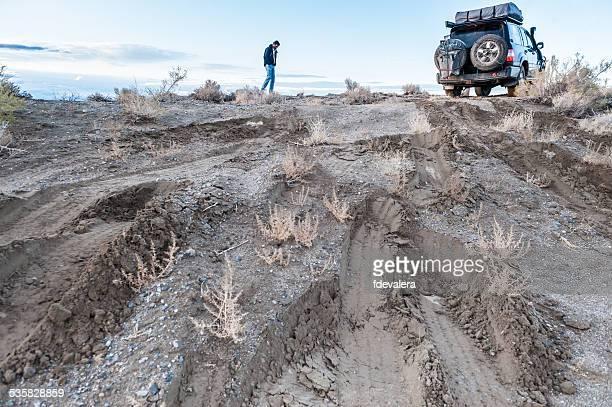 Man checking road conditions on muddy track, Black rock desert, Nevada, America, USA