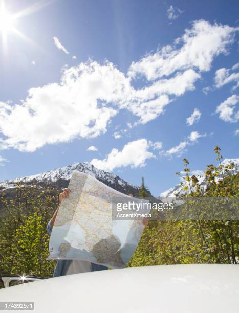 Man checking road map at roadside in mountains