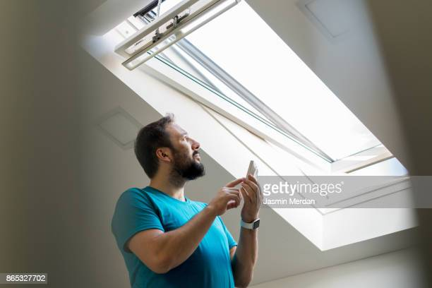 man checking roof window in smart house - energy efficient stock photos and pictures