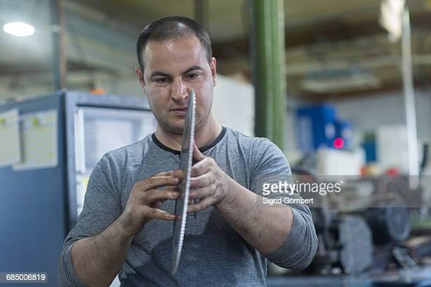 man checking rotary blade in workshop - sigrid gombert stock-fotos und bilder