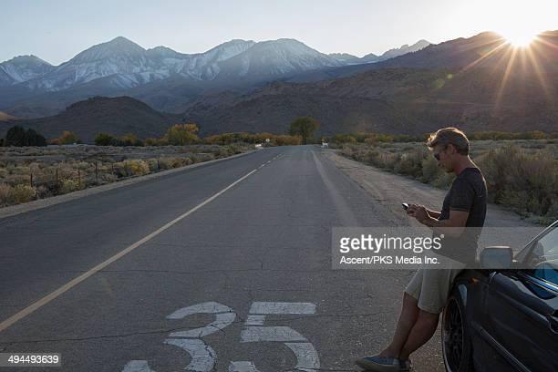 Man checking smart phone at road edge, sunset