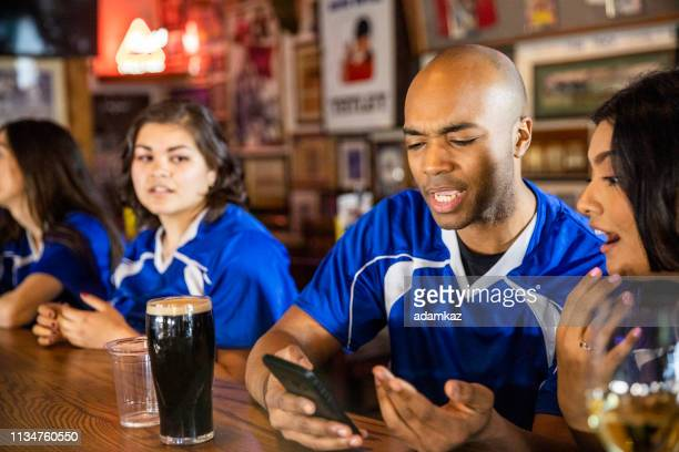 man checking smartphone fantasy football - fantasy stock pictures, royalty-free photos & images