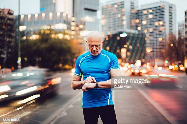 Man checking smartwatch in city.