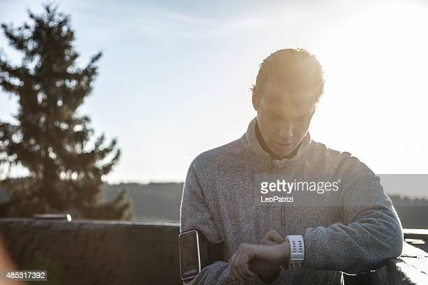 Man checking time after workout on the hills around Oslo