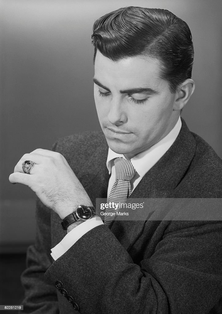 Man checking time, studio shot : Stock Photo