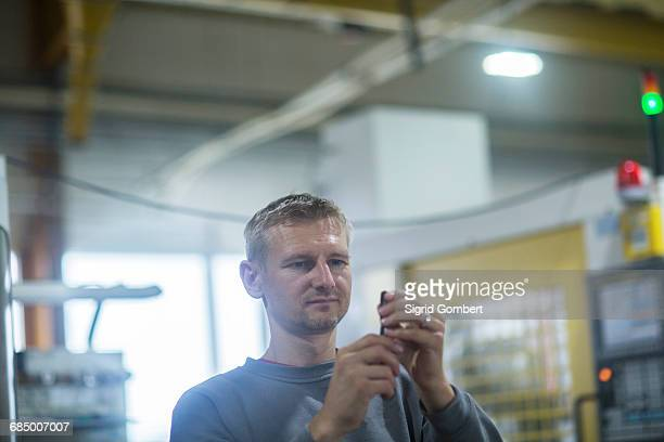 man checking tool in grinding workshop - sigrid gombert foto e immagini stock