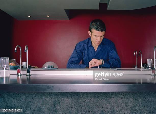 Man checking watch at sushi bar