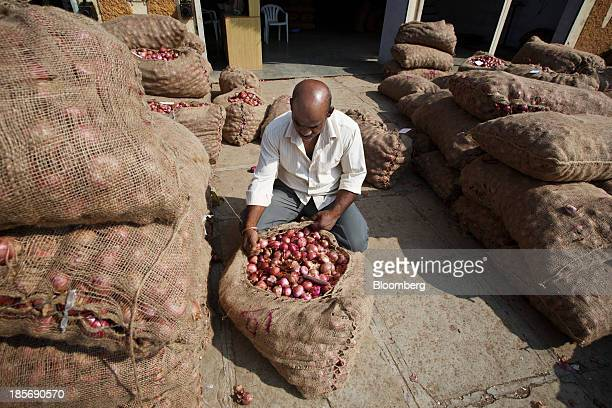 A man checks a bag of onions at a wholesale market in Nashik Maharashtra India on Wednesday Oct 23 2013 Onion prices in India may extend a record...