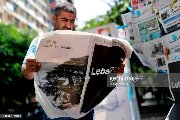 TOPSHOT A man checks a copy of the Lebanese local Englishlanguage newspaper The Daily Star in the capital Beirut on August 8 which refrained from...